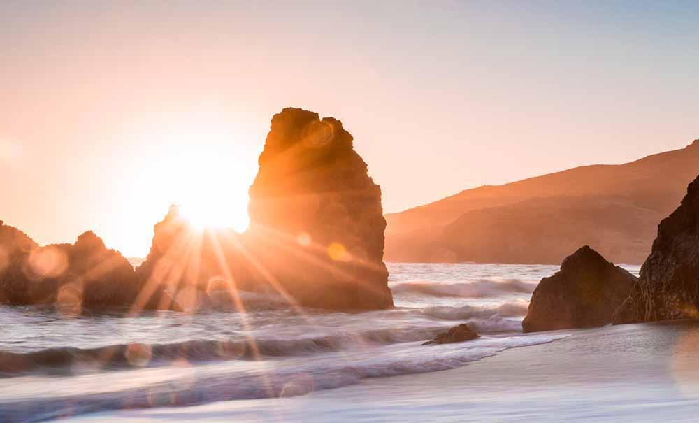 大きな岩の向こうから太陽が輝く海辺