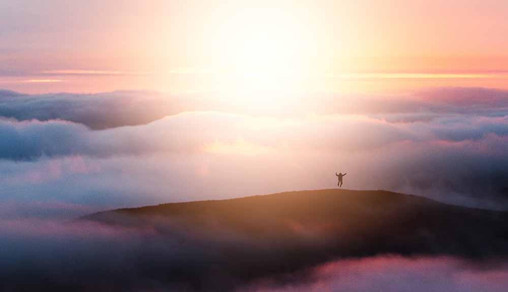 広大な山の上で雲海に刺す太陽の光を浴びて飛び上がる人