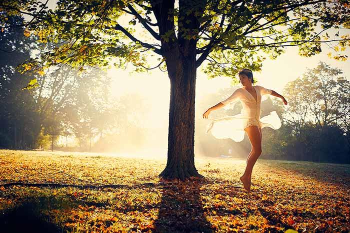 背後に太陽の光が落ちる樹の周りで踊る女性