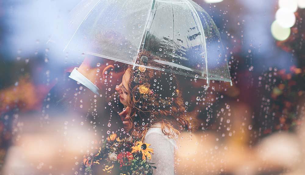 雨の中傘の下で抱き合うカップル
